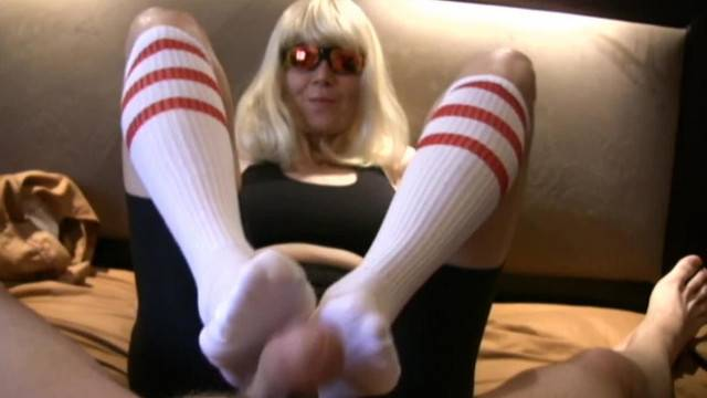 Granny gives her young boyfriend a footjob with her socks on