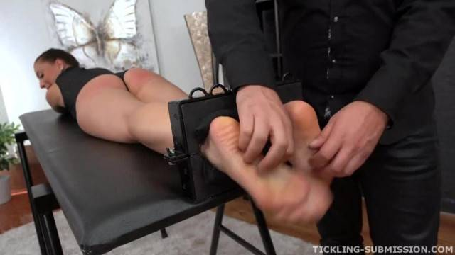 Cute brunette receives tickling punishment while being immobilized on the torture table